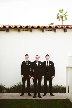 Super dapper groom and groomsmen wearing classic black and white tuxedos!