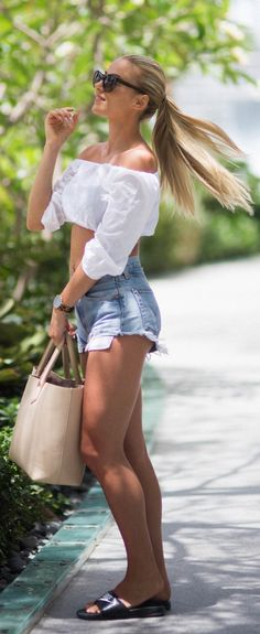 Sendi Skopljak is wearing a white long sleeved crop top with light wash Levi denim shorts, a beige handbag and Nike slippers