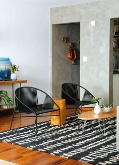 Sala de estar tem parede de cimento queimado, poltronas pretas e móveis de madeira.