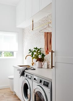 The norsuHOME - Laundry Photographer: Lisa Cohen Stylist: Beck Simon  Paint: Dulux Vivid White Tiles: Perini Tiles Cabinetry: kaboodle Kitchens Flooring: Godfrey Hirst  Benchtop: Caesarstone Appliances: Smeg Tapware: Sussex Taps Sink: ABI Interiors Blinds: Carpet Court