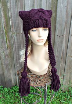 This hat is hand knit of a wool blend yarn in a lovely eggplant purple colour. A playful cable detail runs up the middle of the crown. Two ear flaps with extended ties and fluffy tassels finish off the look!  This knit hat best fits an average adult and teen head of 20 - 23 inches in circumference. We can easily customize it to fit other sizes as well!  Hand wash, dry flat. Every item from Pixiebell is handmade and knit or crocheted to order, unless otherwise stated in title of the item as…