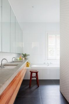 Heavy-grained timber joinery, concrete benchtops and black large-format tiles give the bathroom an understated elegance.