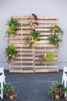 wooden pallet ceremony backdrop with flowers, ferns, and greenery woven in