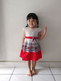 Baby girl's dress. Red white and ribbon. Braided hair. No shoes.