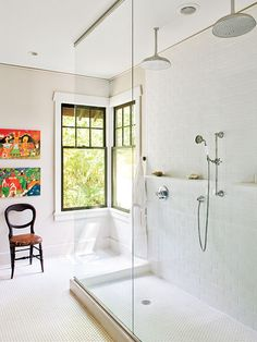 This Georgia bathroom breaks all the rules with windows sans window treatments, no bathtub, and punches of color through artwork. The extra-large shower is enclosed with clear sheets of shatterproof glass. A central storage cabinet sits atop the concrete countertop, separating his-and-hers sinks. Two folk art paintings infuse the space with color and energy. (Photo: Laurey W. Glenn)
