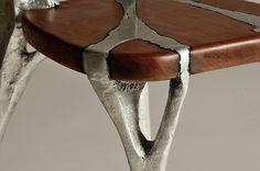 a chair made of cast Aluminium and fine Mahogany wood.one piece - no screws glue or welding. http://urielnatan.wix.com/uriel