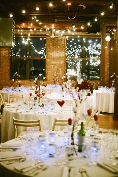 reception hall. also has rose decorations & votives(shown in other photo) on the tables. wedding party sits with guests minus bride & groom who have a sweethearts table. their table has a red cloth, rose petals scattered on it plus the centerpieces the other tables do. also, a vase to place the bouquet in for safe keeping