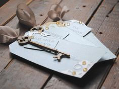 Antique Table Cards we made for a recent wedding! Ribbon brought together the main card with the person's name, a smaller card with their table name, and a unique antique key! ($5 each). #weddings #tablecards