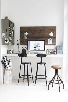 black and white standing desk workspace with black industrial barstools and wood accents