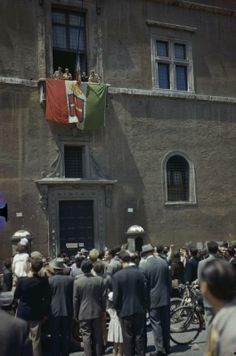 ENTRY OF ALLIED TROOPS INTO ROME, 5 JUNE 1944. Allied troops on the flag draped balcony of Palazza Venezia, from which Mussolini used to address the people of Rome, while people celebrate below them.