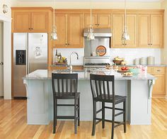 Love this kitchen from Better Homes & Gardens. We're planning to redo our kitchen in white. It's interesting to see the white combined with light brown cabinets and black chairs. Stainless steel appliances are so elegant, and I love the pendant lights.