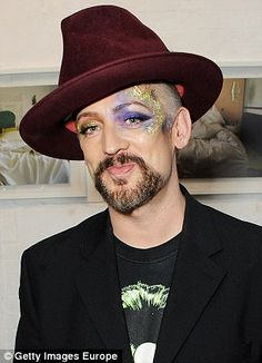 Boy George reveals a thick head of grey hair on US chat show