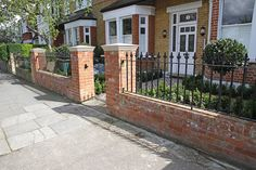 Red Brick Wall And Gate Posts With Cast Iron Black Railings In Front Garden.