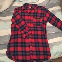 Hollister Plaid Shirt Red and navy blue Hollister brand shirt with bead embellishment. Received as a gift but never worn because it isn't my size. Great condition and super cute! Hollister Tops Button Down Shirts