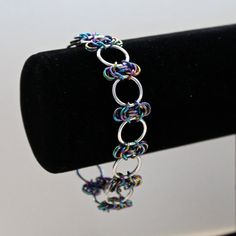 Handmade chainmaille Byzantine weave bracelet in black rainbow and silver.  This bracelet is a byzantine weave of black rainbow sections, joined with large silver aluminium jump rings, which fastens easily and securely with a stainless steel lobster clasp. The bracelet is 8 inches long. If you would like a different length chain, please just leave me a message at checkout with the length you would like. (A good way to measure your wrist is to wrap a piece of string around your wrist, or just…