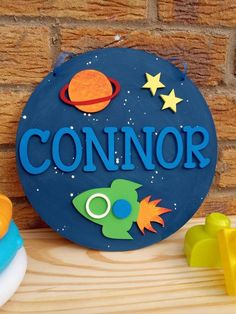 Hand-painted circular plaque with a space theme and personalised with the name of your choice.