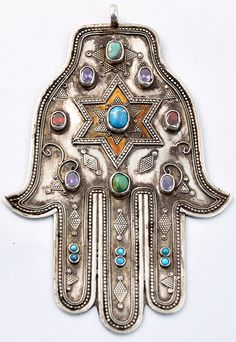 "A hamsa is an amulet shaped like a hand, with three extended fingers in the middle and a curved thumb or pinky finger on either side. It is thought to protect against the ""evil eye"" and is a popular motif in both Jewish and Middle Eastern jewelry. Hippie Style, Turquesa E Coral, Hand Der Fatima, Estilo Hippie, Hippy Chic, Boho Chic, Jewish Art, Tribal Jewelry, Hamsa Jewelry"