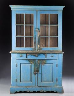 """PAINTED FLATWALL CUPBOARD.  Probably southern Indiana, mid-19th century, poplar with old worn blue over earlier yellow. One-piece cupboard, nicely detailed with bold cornice, original square wood knobs, chamfered corners, and scalloped skirt.  78""""h. 47 1/2""""w. 20 1/2""""d."""