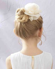 coiffure petite fille - petit chignon torsadé, orné d'une fleur blanche délicate