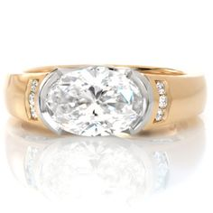 This custom ring is uniquely designed to hold a 1.50 carat oval cut diamond horizontally in a platinum half-bezel setting. The high polished 14K yellow gold band features vertical channel set diamonds.  www.knoxjewelers.biz Filigree Engagement Ring, Three Stone Engagement Rings, Vintage Engagement Rings, Halo Engagement, Diamond Studs, Diamond Jewelry, Oval Diamond, Diamond Rings, Contemporary Engagement Rings
