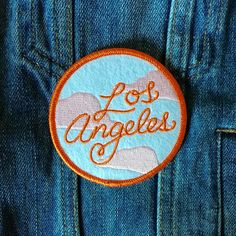 "An ode to my favorite city in the world: LA has the most beautiful pink pollution. 3"" x 3"", duo tone embroidery on felt. Iron-on backing."