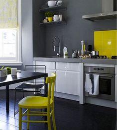 Cuisine contemporaine ou le gris anthracite de la peinture murale s'oppose au jaune vif du carrelage de la crédence et celui des chaises.