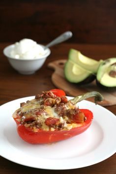 Cowboy Chili Stuffed Peppers- 2 tbsp coconut oil, 1/2 small onion,1/2 tsp salt, 2 cloves garlic, 2 tbsp chili powder, 2 tsp cumin, 2 tsp paprika, 1 tsp black pepper,  1/2 tsp cayenne,1 lb ground beef, 1 28-ounce can diced tomatoes, 1/2 cup beef or chicken broth, Salt and pepper to taste, 4 medium sweet peppers, 1 cup shredded Cheddar cheese+