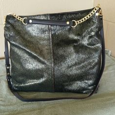 Cow hair and leather purse hobo style Has long and short strap Cow hair has a gold sheen to the black color Tag says gold haircalf Size 15 in high x 14.5 in wide x 5 in deep Gold chain Bought at dillards I think this looks better than Michael Kors Richard looking and unique ANTONIO MELANI Bags Hobos