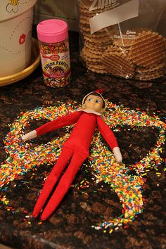 Elf on the Shelf making snow angel from sprinkles