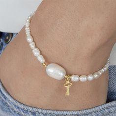 Pulsera de Perlas de río con colgante en forma de llave, bolitas, cierre y cadena extensora de Plata de Ley con baño de oro. Hecho a mano.