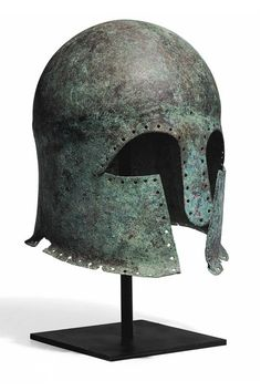 A GREEK BRONZE CORINTHIAN HELMET  ARCHAIC PERIOD, CIRCA MID 6TH CENTURY B.C.  Hammered from a single heavy sheet, of domed form, the neck-guard flaring, with elongated almond-shaped eye holes and a protruding rounded nose-guard, the bowl carinated horizontally, perforated along the perimeter, additional perforations centered low on the brow and one toward the back on either side; an ancient repair reinforcing the nose-guard