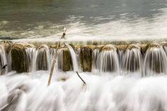 Ein Wehr wird von Wasser überströmt – weiches Wasser lässt das Foto malerisch wirken. Auf dem lange belichteten Foto erscheint das Wasser wie ein Schleier. Mehr zu Technik und Tricks: www.fotos-fuers-leben.ch