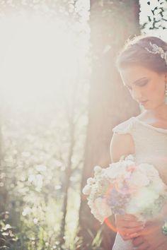 Los rayos del sol iluminan delicadamente a nuestra novia dando un toque romántico a la fotografía.