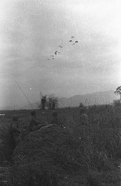 Dans une tranchée, quatre parachutistes observent le parachutage de renforts lors de la bataille de Diên Biên Phu. Date : Mars 1954