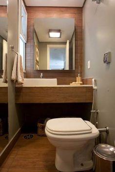 Banheiro com bancada, parede atrás do espelho e piso em porcelanato que imita madeira.