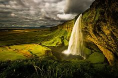 SELJALANDSFOSS, ICELAND  Photograph by Howard Ignatius  Seljalandsfoss is located between Selfoss and Skogafoss on the Southern Ring Road (Iceland's main highway) down to Vik. The picturesque waterfall plummets 60 m (200 ft) to a deep pool below. Visitors can even hike around the pool to the back of the falls for a…