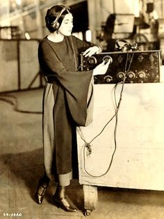 Silent film start Nita Naldi listening to a fellow Italian singing an operatic selection on the radiophone in a California studio, 1922.