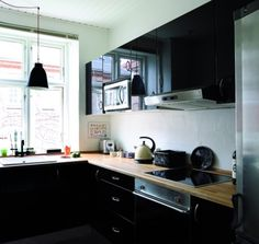another impressive black kitchen. No way are my old cabinets getting this high-gloss treatment, though.