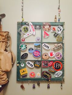 Repurposed an old window. Added a chain for hanging and hooks for additional display.  Then added my husbands collection of beer stickers, pins and key chains