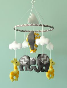 This Elephant Mobile is MADE TO ORDER This mobile consists of 2 Elephants and 2 Giraffes in lemon yellow/grey made with premium wool blend felt. Above each animal is a cloud. Hanging in the centre is a hot air balloon using the same colours used on the elephants. PERSONALISE If you