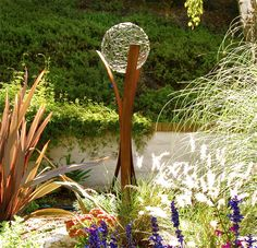 Gazing balls were popular in Victorian gardens, but this wood and glass piece is a modernistic twist on an old favorite.  This clear glass piece would look great in a yard no matter what the season.  For all-season #Landscape Design in MN, visit us at http://www.aldmn.com