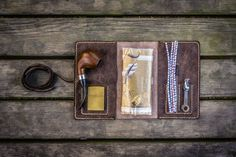 Personalized Leather Pipe Pouch - Rustic Dark Brown. Handmade Minimalist Leather Pipe Pouch Good quality brown aged leather. Hand stitched with waxed polyamide thread.The edges are beveled, waxed and burnished for a finished look. This pouch features 2 large pockets, to fit pipe and/or a 1-2 ounce pouch of tobacco. Small separate pockets hold a lighter, 1-2 tampers and some pipe cleaners, and your accessories never touch your pipes. The leather string hold everything in place when the…