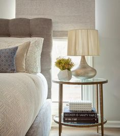 Chic bedroom features a gray button tufted headboard on bed dressed in white and gray geometric bedding placed next to a round forged metal and glass bedside table, Crate & Barrel Round Clairemont Round Side Table and a silver leaf lamp.