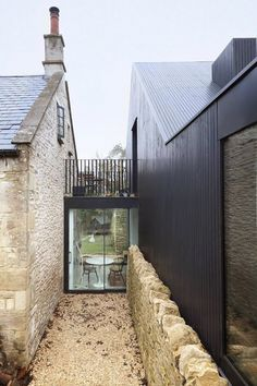 Combining stone chapel with timber sided extension via glass and steel.