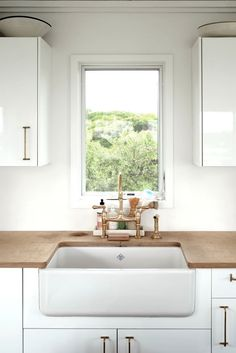 White lacquered cabinets, brass hardware, butcher block counters and farmhouse sink.
