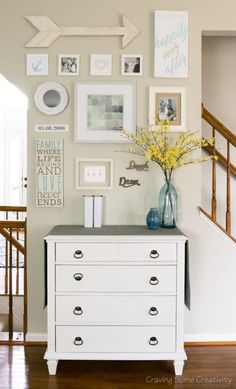 Easy watercolors and DIY art are used to create this personalized happily ever after gallery wall in the living room between the stairs. The layout also hides an awkward outlet.