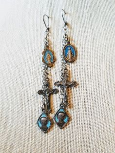 A beautiful pair of lever back dangle earrings. Two different crucifixes and four different blue enamel French religious medals dangle from delicate silver tone chains. Vintage statement assemblage earrings, one of a kind handmade vintage assemblage earrings, upcycled French enamel religious medals earrings, Catholic assemblage earrings, Christian assemblage earrings. Note: the French enamel medals have no visible chips.