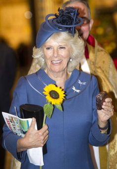 Festive: The Duchess of Cornwall wore a blue suit and carried a sunflower as she admired the harvest produce celebration. Pretty fancy brownie in her hand too! Love this shade of blue, her hat and the dragonfly pins. Camilla Duchess Of Cornwall, Camilla Parker Bowles, Prince Phillip, Save The Queen, Prince Of Wales, Queen Elizabeth Ii, Duke And Duchess, British Royals, Diana