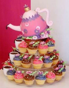 """Today's cupcake features a kettle tea fountain. The huge pink kettle """"pouring"""" chocolate onto cups next to the colorful and prettily decorate flower cupcakes is just amazing! Alice in Wonderland anyone?"""