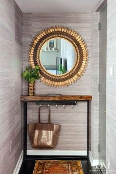 Love this small, yet elegant entryway. Beautiful grasscloth and a bold mirror dress up the small space, while the shallow table and hooks up the function factor!